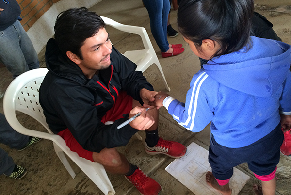 Tennis player Matt Mendez notes this young Bolivian girl's shoe size on her hand.
