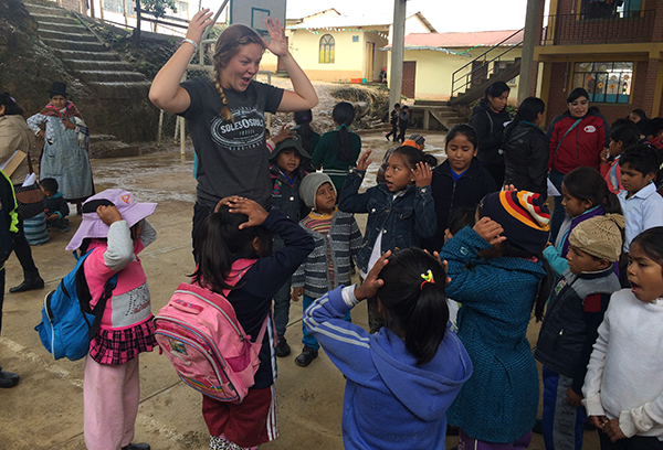 Rower Chelsea Harpool plays a game of Simon Says with a group of Bolivian children.