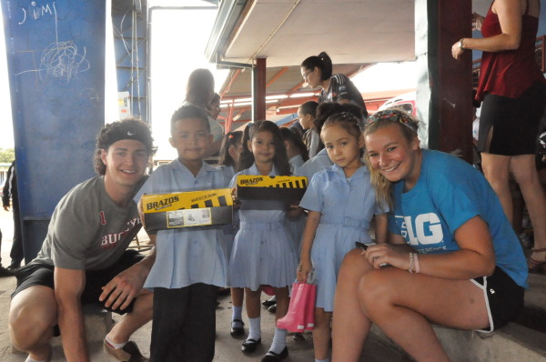 Sam Jardine of men's hockey and Chelsea Quinn of field hockey take a picture with Costa Rican children holding on to their shoe boxes.