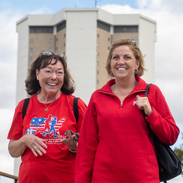 Two women walk outdoors in front of Lincoln Tower at The Ohio State University