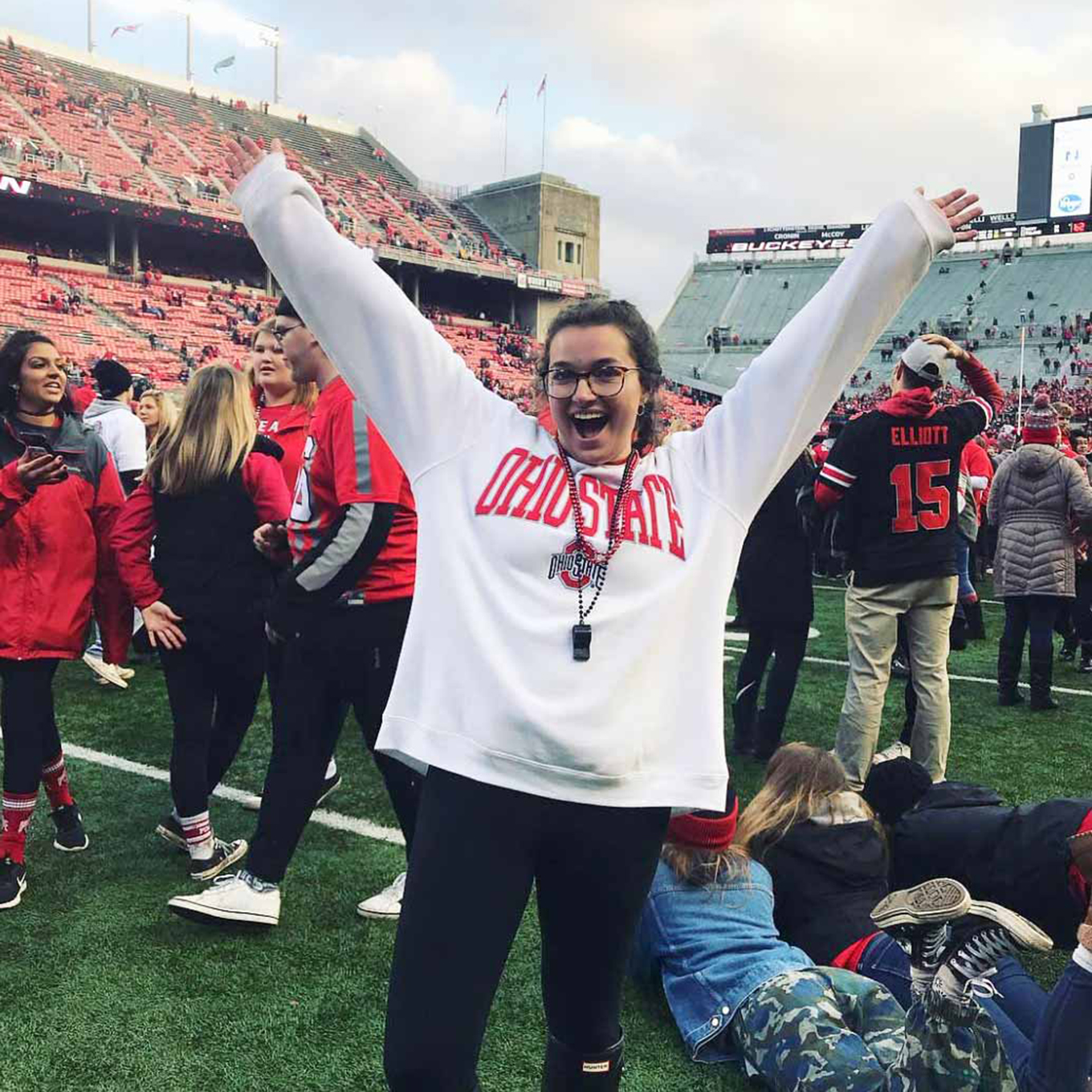 A young woman celebrates an OSU Football victory from the middle of the field.