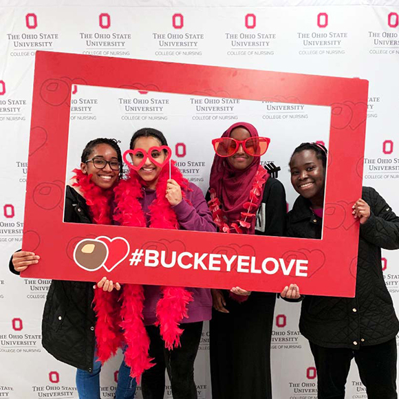 Four young women take a photo with the #BuckeyeLove photo outline at a photo booth.