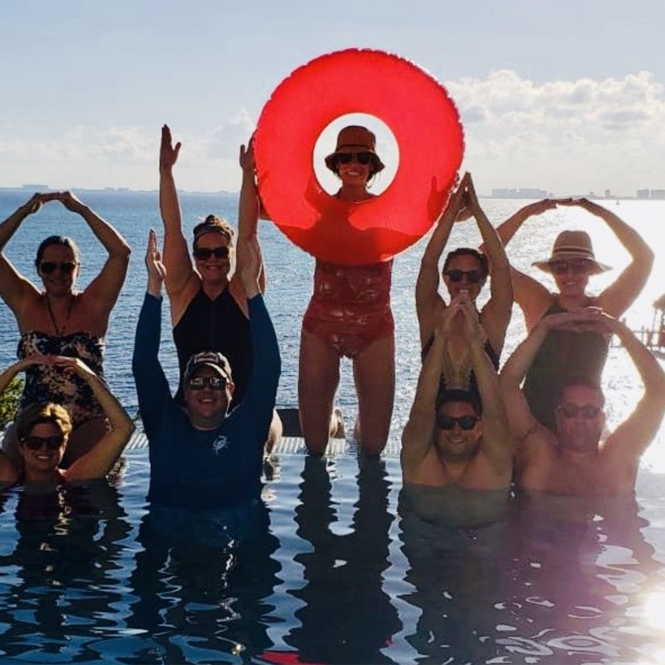 Friends form the O-H-I-O while in a pool in a warm climate