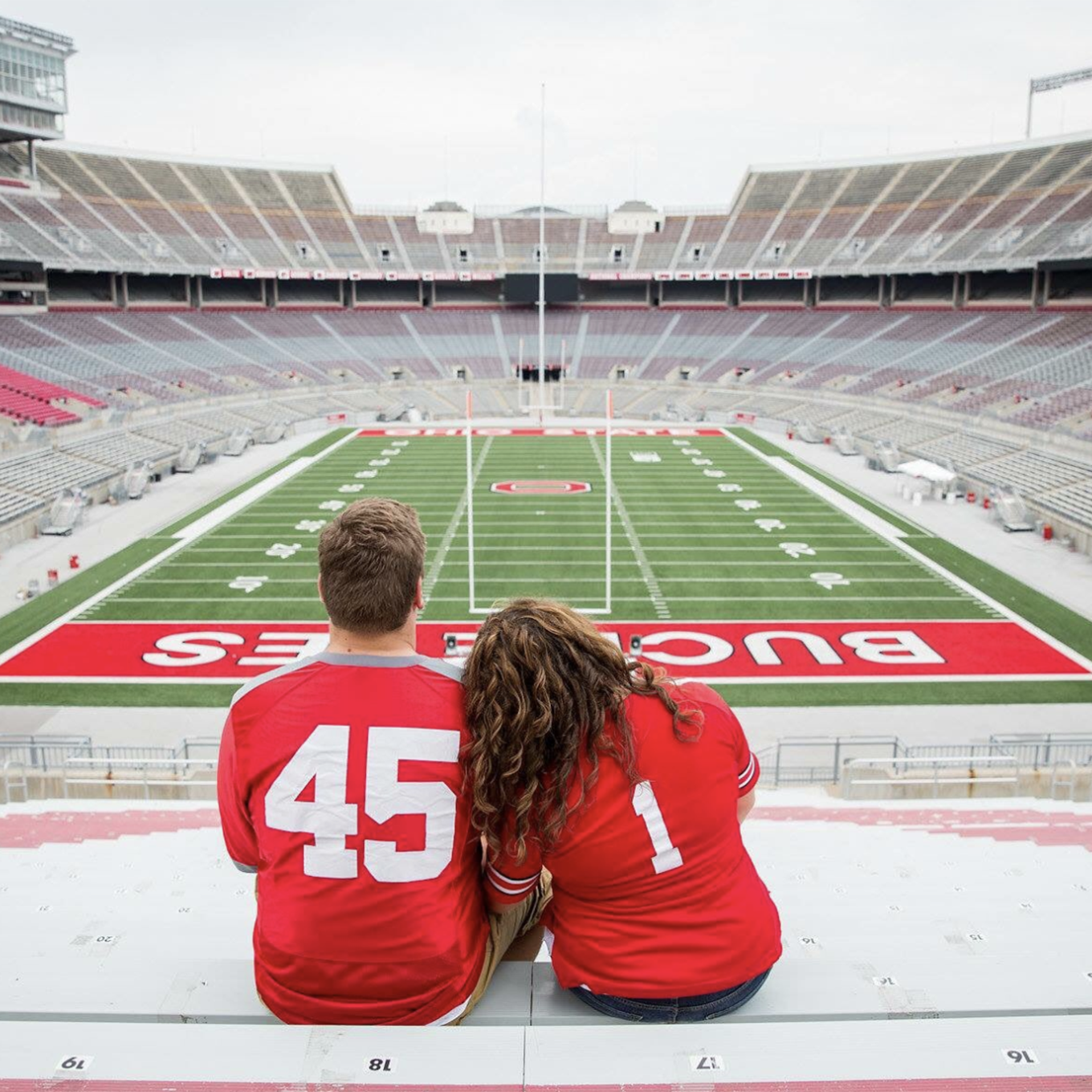 A couple snuggles in the student section of Ohio Stadium while looking onto the field
