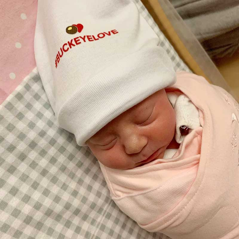 A newborn baby wears a hat that says '#BuckeyeLove'.