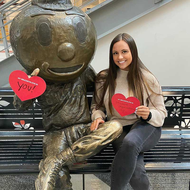 A photo featuring Dana Gill holding paper hearts with a Brutus statue.