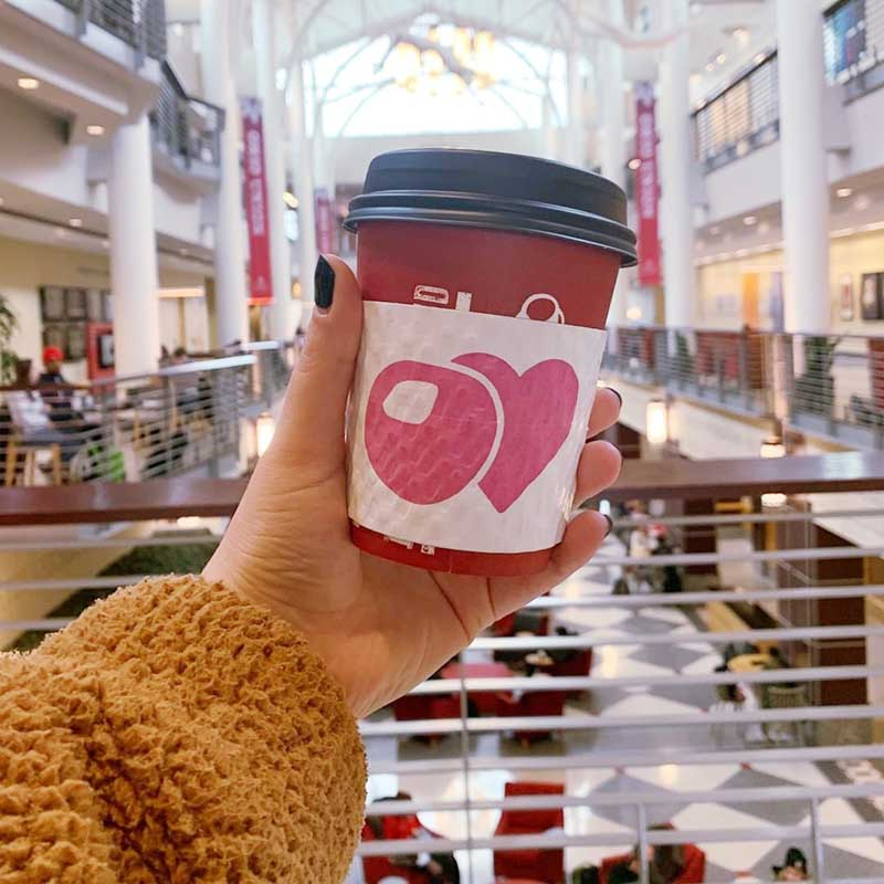 A photo featuring an out-stretched hand holding a cup of coffee with the Buckeye Love logo.