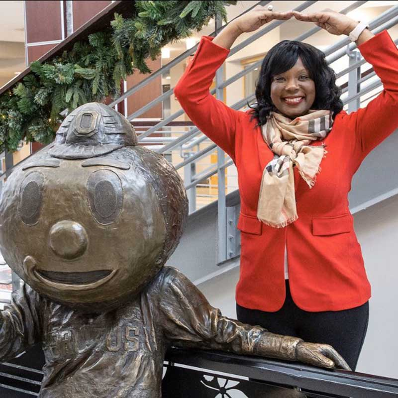 A photo featuring Melissa S. Shivers, PhD. making O with arms by a Brutus statue.