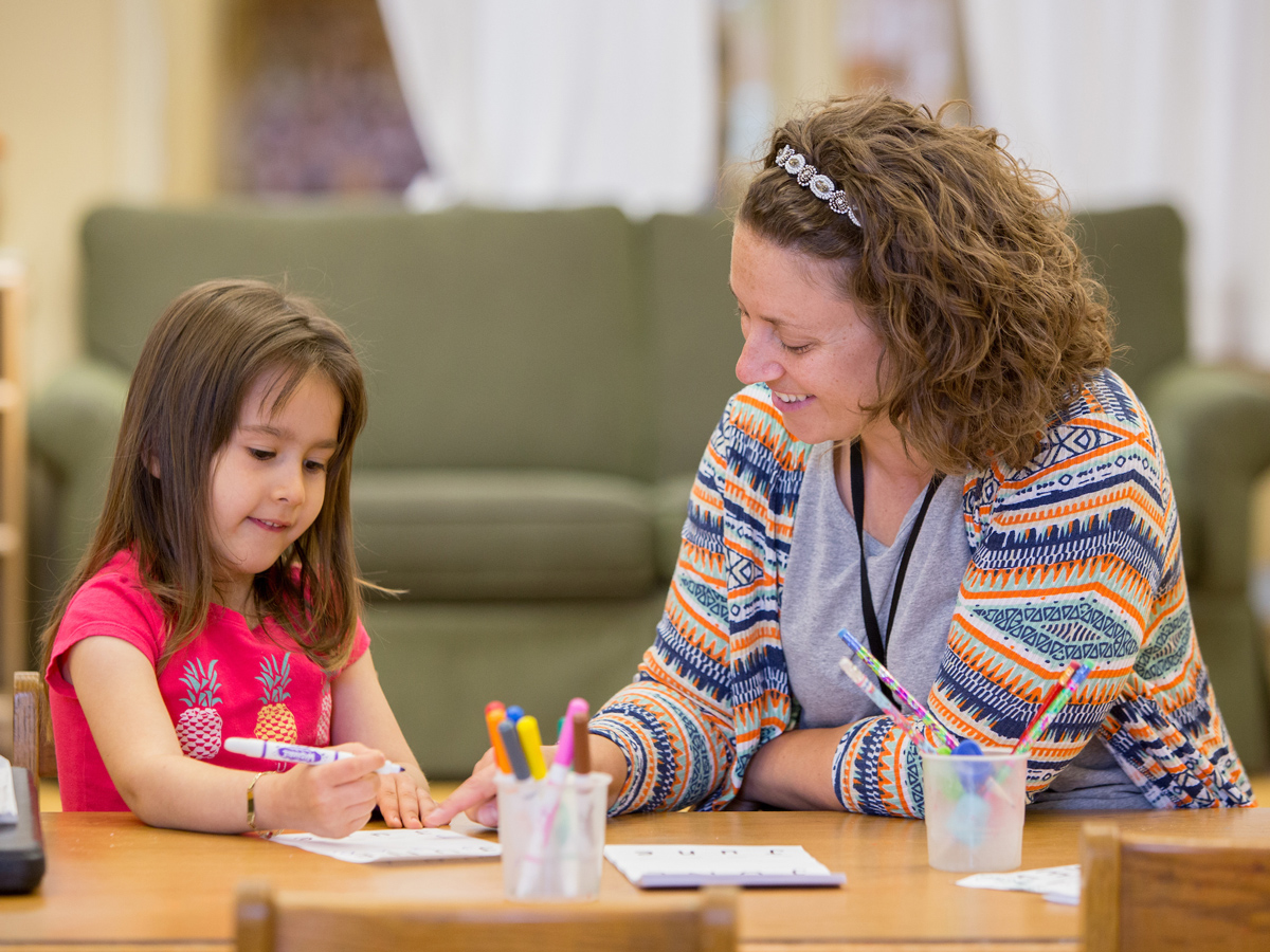 A child and a teacher work on a creative task together at a desk