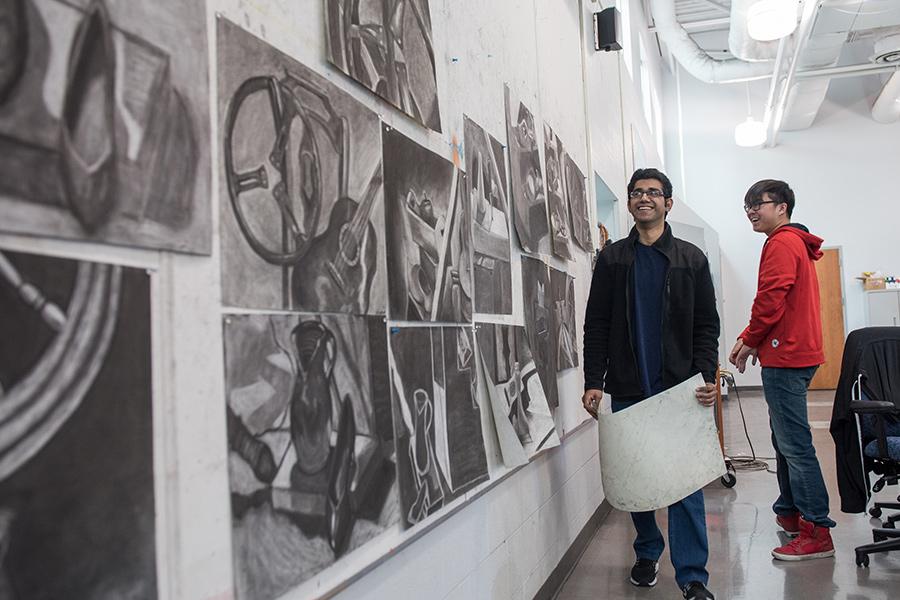 Two men looking at an indoor arts exhibit.