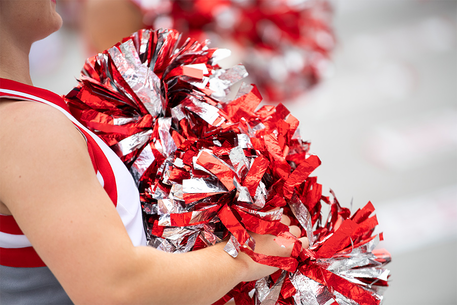 A cheerleader holding red and silver pompoms.