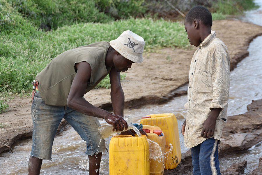 Two men siphoning water from a stream into yellow buckets.