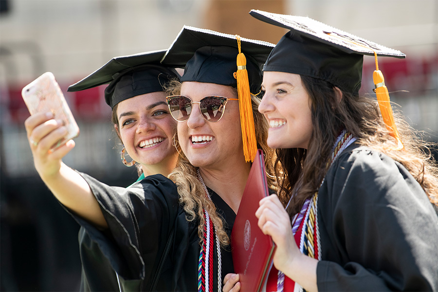 Three students wearing graduation caps and gowns taking a selfie.