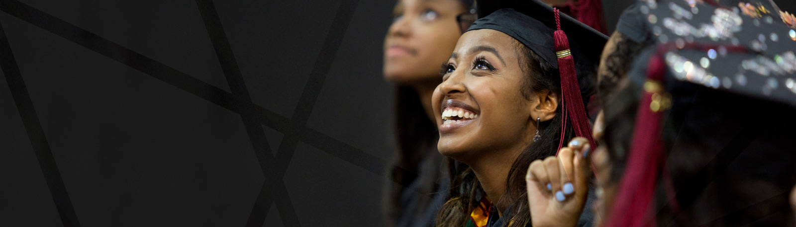 An Ohio State student smiles and looks up during Commencement.