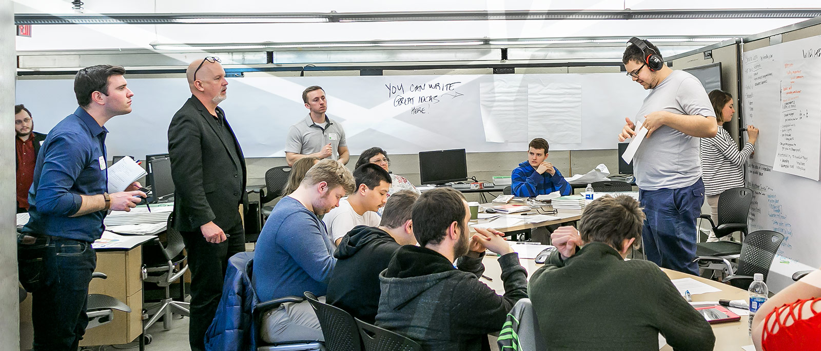 Ohio State faculty member Kyle Ezell looks on as students present their findings and collaborate during a brainstorm session.