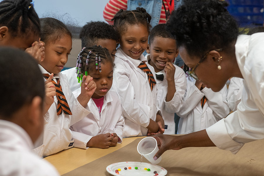 Schoolchildren from the Near East Side of Columbus huddle around a table while wearing white doctor's coats.