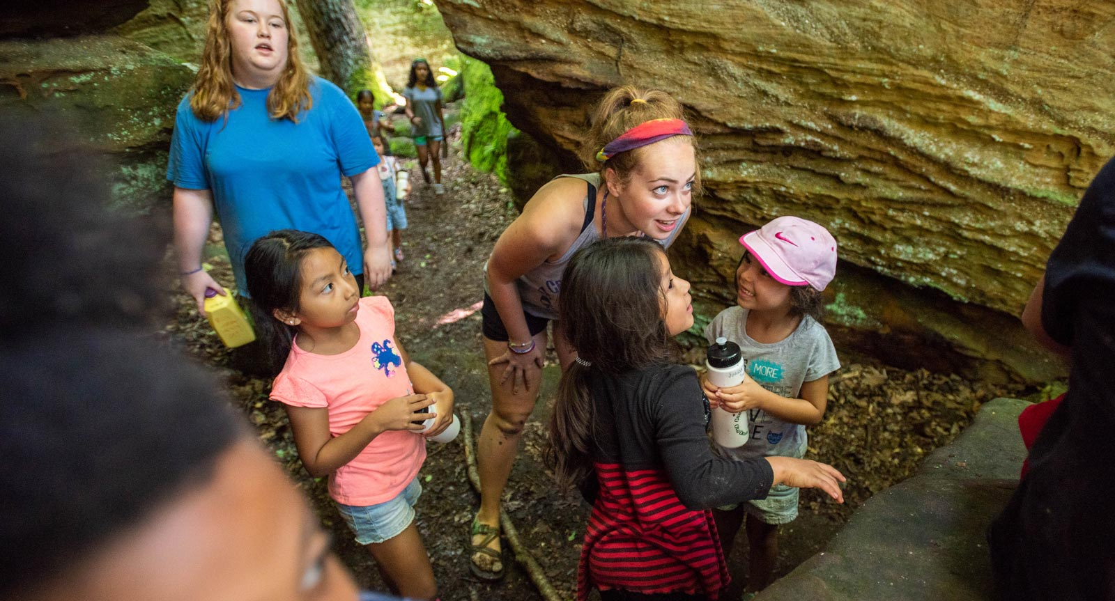 An Ohio State student talks to two children during an outdoors excursion.