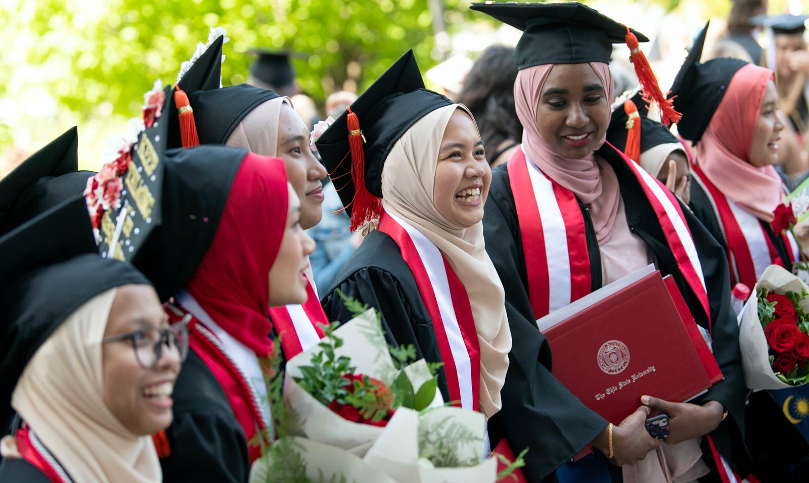 Ohio State students in hijabs smile during a Commencement ceremony.