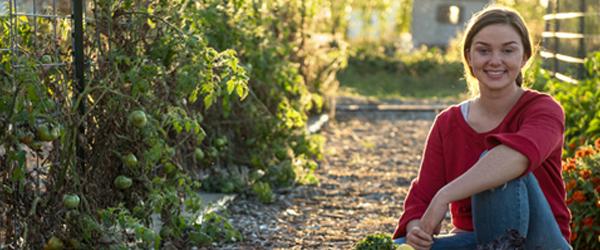 Maggie Griffin kneeling in a vegetable garden